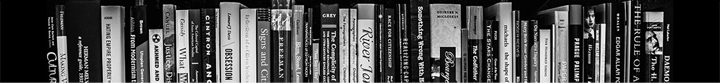 A black and white image of the spines of various books.